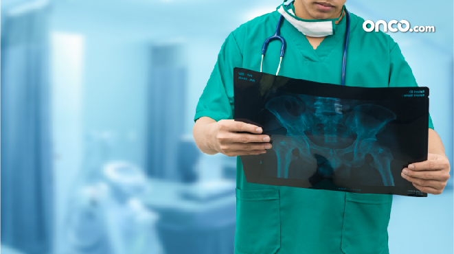 Photograph of surgeon reviewing post-operative reports for stage 4 throat cancer treatment