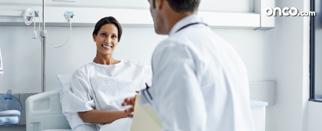 Smiling patient looking at doctor sitting on bed